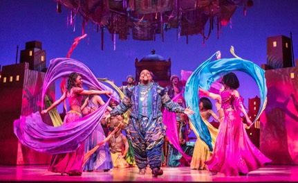 07 Genie (Trevor Dion Nicholas) in market surrounded by scarfs - photo by Johan Persson � Disney